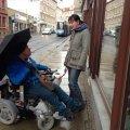 In leichter Sprache - Über einen Rundgang | nicht immer Rollstuhl gerecht. Daniela Nuß mit Besucher vor dem Laden.